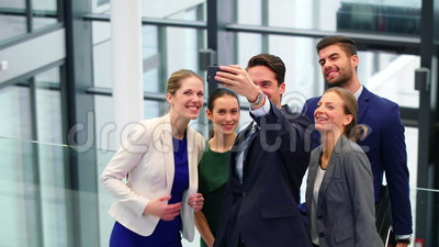 Ejecutivos de operaciones que toman el selfie en el teléfono móvil en pasillo metrajes