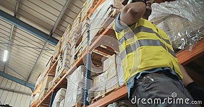 El ángulo bajo tiró de un trabajador de la logística en un almacén grande almacen de video