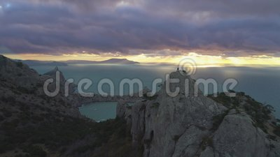 El abejón es vuelo posterior rápido sobre el hombre del escalador que se coloca encima de roca en la salida del sol Silueta del h almacen de video