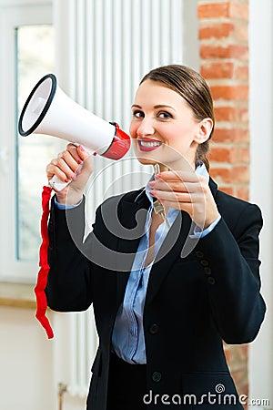 El agente inmobiliario joven está con llaves en un apartamento