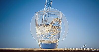 El agua azul está fluyendo en el vidrio que forma burbujas y salpica