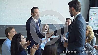 El apretón de manos de dos hombres de negocios durante la reunión Partners el concepto del acuerdo, Boss With Team Of Businesspeo almacen de metraje de vídeo