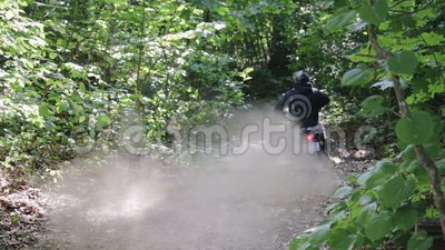 El atleta con equipo de protección en una motocicleta Enduro comienza, el polvo y la moscas de la suciedad salen de debajo de las metrajes