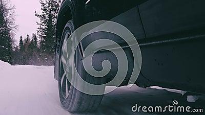 El auto se mueve en una carretera boscosa nevada almacen de metraje de vídeo