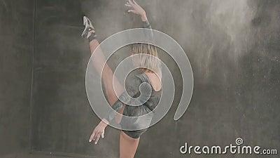 El bailarín de ballet de sexo femenino en traje del cuerpo negro se realiza en etapa al teatro y usar el polvo blanco o al bailar almacen de metraje de vídeo