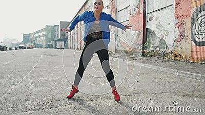 El baile rubio de la mujer realiza la danza moderna que presenta, estilo libre del hip-hop en la calle, urbana cantidad de la acc metrajes