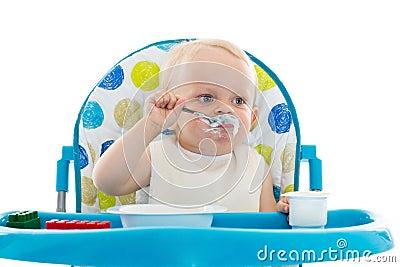 El bebé dulce con la cuchara come el yogur.