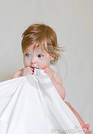 El bebé lindo muerde el borde blanco del paño