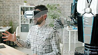 El brazo humano y robótico haciendo los mismos movimientos, el tipo en la máquina de prueba de vasos vr metrajes