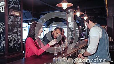El camarero da el tubo de la bebida en muchacha de la diversión dos almacen de metraje de vídeo