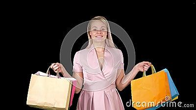 El caminar iwhile sonriente feliz de los bolsos de compras de la mujer que celebra que hace compras, Alpha Channel almacen de video