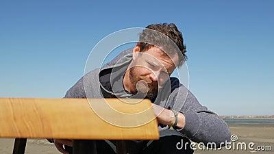 El carpintero con una barba y un bigote contra un cielo azul toca la superficie de la tabla, hecha por él a mano handmade almacen de metraje de vídeo