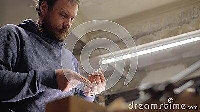 El carpintero experto profesional muele el peine de madera de la barba con el papel de rasguño artesano handmade 4 K almacen de video