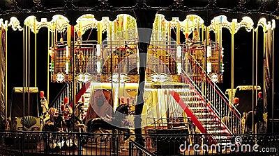 El carrusel de niños de época iluminado en un parque de atracciones por la noche metrajes