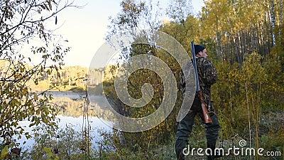 El cazador camina por el lago almacen de metraje de vídeo