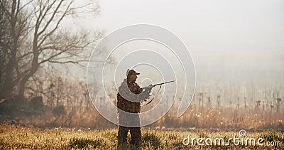 El cazador en el equipo de la caza apunta la blanco con el rifle en el campo a la mañana de niebla o a la tarde soleada del otoño metrajes