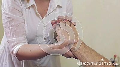 El cierre para arriba de las manos de la masajista hace el masaje de la muñeca de la mano al hombre adulto healing almacen de video
