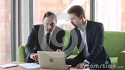 El cliente asesor del agente de sexo masculino con el apretón de manos del ordenador portátil hace trato metrajes