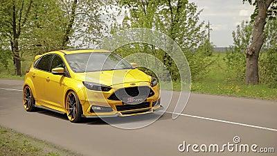 El coche amarillo-naranja de los deportes se mueve a lo largo de un callej?n hermoso con los ?rboles y los neum?ticos discretos d almacen de video