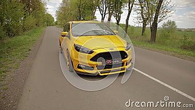 El coche amarillo-naranja de los deportes se mueve a lo largo de un callej?n hermoso con los ?rboles y los neum?ticos discretos d metrajes
