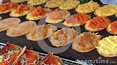 El cocinero al aire libre que cocinaba el aperitivo tailandés tradicional coció paquetes del arroz al vapor con el relleno de tie metrajes