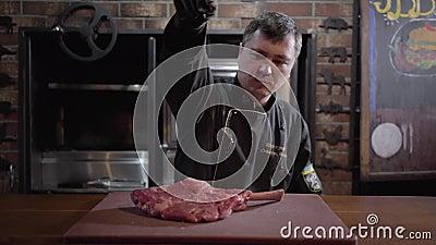 El cocinero pone un pedazo de carne crudo, jugoso en una tabla de cortar y lo sala por todos los lados mientras que se coloca en  almacen de metraje de vídeo