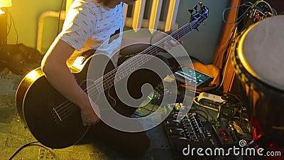 El comprador está probando una nueva guitarra al comprar un instrumento musical almacen de metraje de vídeo
