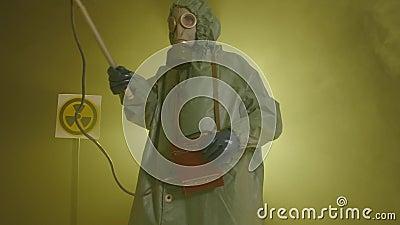 El concepto de desastre ambiental y contaminación por radiación. Un hombre con traje de protección contra la radiación mide la almacen de metraje de vídeo