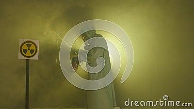 El concepto de desastre ambiental y contaminación por radiación. Un hombre con traje de protección contra la radiación mide la metrajes