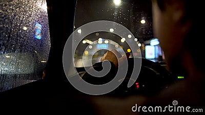 El conductor que come detrás volante adentro el coche parqueado por el camino de ciudad almacen de video