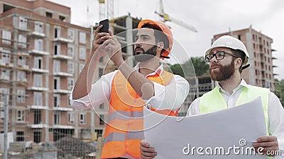 El constructor y el arquitecto en emplazamiento de la obra que fotografían con samrtphone y que comprueban con plan de la constru almacen de video