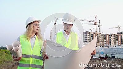 El constructor y arquitecto hombre y mujer discuten el plan de construcción del moderno centro de negocios situado cerca metrajes