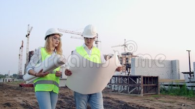 El constructor y arquitecto hombre y mujer discuten el plan de construcción del moderno centro de negocios situado cerca almacen de metraje de vídeo