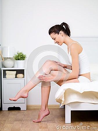 El cuidar sobre la pierna de la mujer con crema