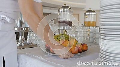 El desayuno bufé está disponible para el almuerzo Cierre de las manos de los camareros, colocando en la mesa un plato de fruta almacen de video