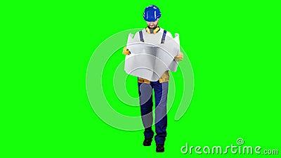 El diseñador con el dibujo en sus manos va en el objeto y mira alrededor Pantalla verde almacen de metraje de vídeo