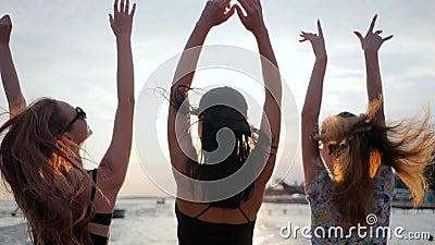 El disfrute de la vida, mujeres jovenes de la felicidad baila en el mar brillante en vacaciones, muchachas del fondo se divierte  metrajes
