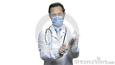 El doctor maduro con el estetoscopio pone en máscara protectora almacen de metraje de vídeo