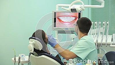 El doctor muestra en el monitor los dientes sanos del paciente almacen de video