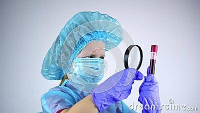 El doctor, un niño, sostiene un tubo de prueba en su mano con los análisis y lo mira. Él se asemeja a través de una magnificación almacen de metraje de vídeo