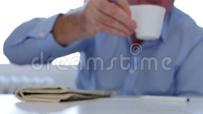 El empresario aburrido y cansado bebe una taza de café caliente y de activación metrajes