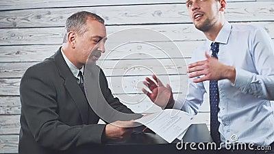 El encargado joven sonriente persuade a un cliente de firmar un contrato almacen de video