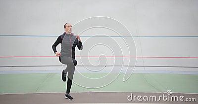 El entrenador deportivo se está calentando La mujer se arrodilla mientras corre en su sitio en el exterior, en el fondo blanco almacen de video