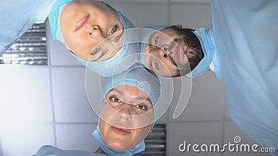 El equipo de cirujanos serios se enfrenta a mirar al paciente despertándose después del coma, monitorizando metrajes