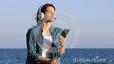 El escuchar de relajación de la mujer la música en la playa