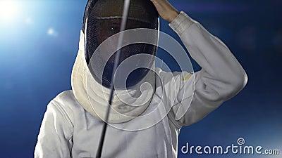 El esgrimista se pone máscaras y se convierte en una postura de combate de esgrima almacen de metraje de vídeo