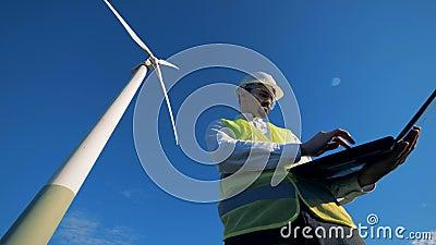 El experto de la energética está navegando su ordenador mientras que se coloca cerca de un molino de viento Energía alternativa r almacen de video