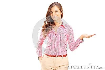 El gesticular femenino sonriente con su mano y mirada de la cámara