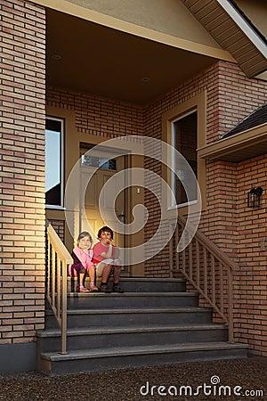 El hermano y la hermana se sientan en las escaleras cerca de puerta