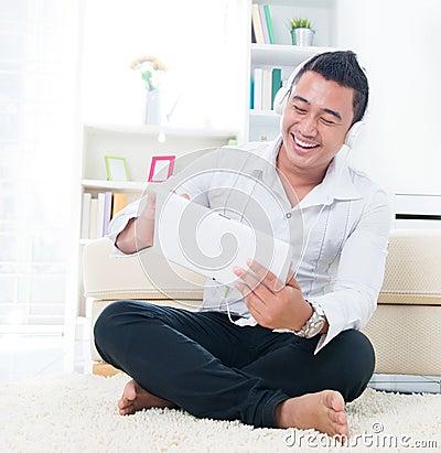 El hombre asiático escucha canción con el auricular